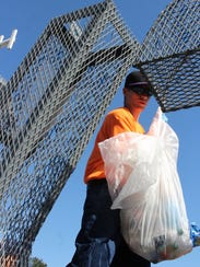 A Grant Parish inmate reaches for trash to drop into
