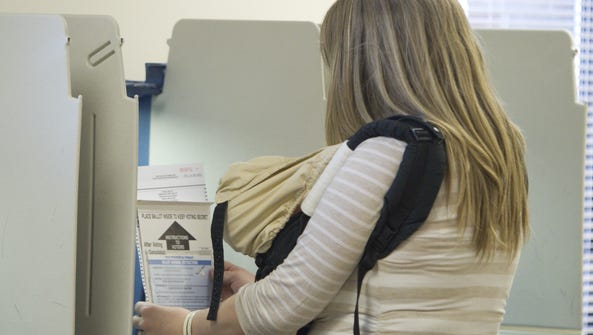 Katee Cole puts her primary ballot in a protective