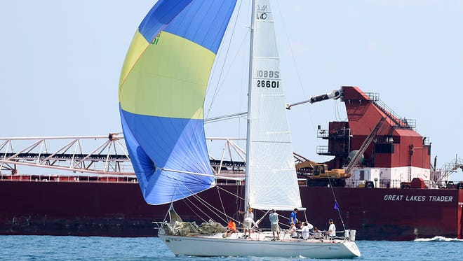 A helicopter with a photographer taking pictures and a freighter pass by a sail boat as it was about to race with others in the start 9 of the PHRF E Division 3 Shore Course during the 2014 Bell's Beer Bayview Mackinac Race on July 12, 2014.