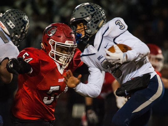 Lenape defensive lineman Aaron Acosta (54) goes for a hit on Howell quarterback Eddie Morales III (3) at Lenape Regional High School on Friday, November 17.