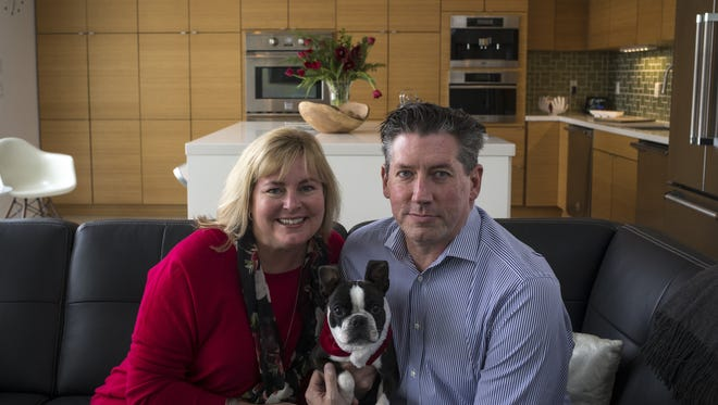 Julia and John Francis and their dog, Jiggs, in the great room of their south Scottsdale home.