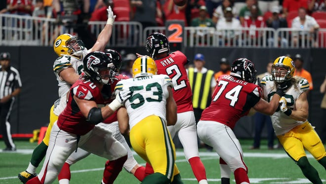 Packers defensive end Dean Lowry (94) tries to pressure Falcons quarterback Matt Ryan (2) as he passes to running back Tevin Coleman (26) for a touchdown late in the first half.
