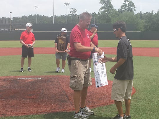 Fairview coach Brent Dowies (right) receives a game ball from an LHSAA official after his team won the Class B title in Sulphur.