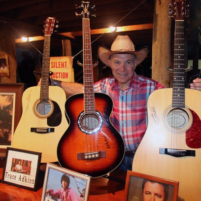 Milt Kostuk with guitars signed by Trace Adkins, Arlo