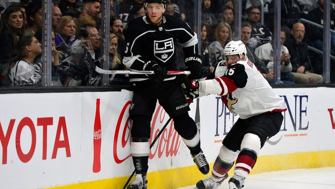 February 3, 2018; Los Angeles, CA, USA; Los Angeles Kings left wing Adrian Kempe (9) clears the puck as Arizona Coyotes center Brad Richardson (15) moves in with a hit during the first period at Staples Center. Mandatory Credit: Gary A. Vasquez-USA TODAY Sports