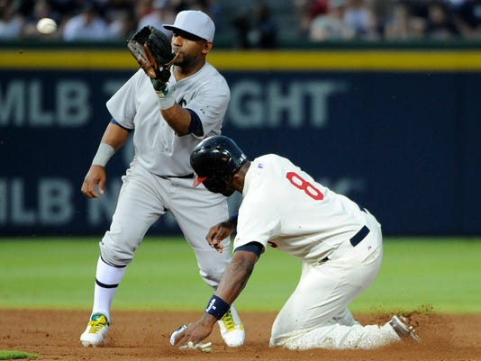 Atlanta Braves' Justin Upton (8) is safe at second base as Oakland Athletics' Alberto Callaspo fields the late throw on a wild pitch during the fourth inning of a baseball game Saturday, Aug. 16, 2014, in Atlanta. (AP Photo/David Tulis)