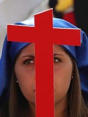 Una mujer sostiene una cruz color rojo esperando al Papa Francisco en su recorrido.