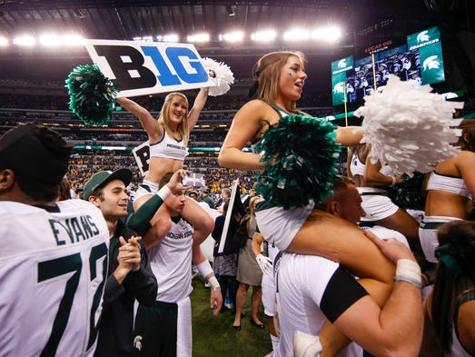 Michigan State cheerleaders hold up signs in celebration