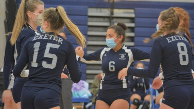 Exeter's Ally Childs (15), Eva Melecio (6) and Grace Kelly (8) celebrate with teammates after a getting a point in Monday's season-opening volleyball match against Winnacunnet in Hampton.