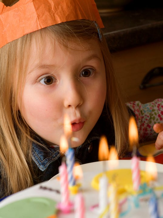 Close-up of a girl blowing out candles on her birthday cake