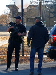Police keep watch near the entrance of Aztec High School