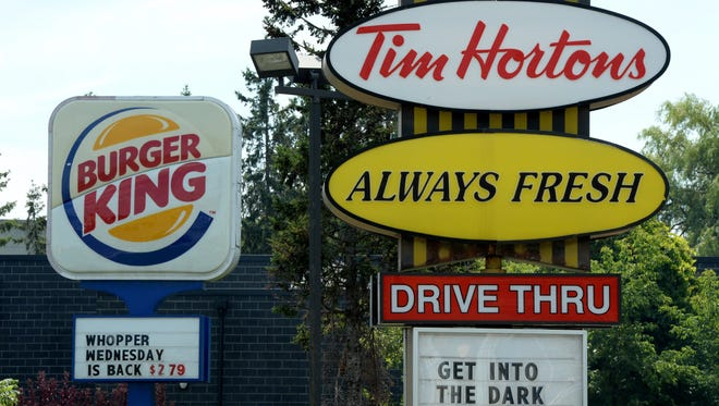 A Burger King sign and a Tim Hortons sign are displayed in Ottawa, Ontario, Monday, Aug. 25, 2014. Burger King is in talks to buy Tim Hortons in hopes of creating a new, publicly traded company with its headquarters in Canada.