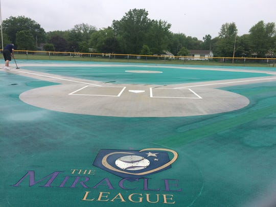 Miracle League of Green Bay executive director Paul Liegeois, top left, sweeps away standing water on Resch Miracle Field at Allouez Optimist Park on Friday afternoon, May 27, 2016, after a rainstorm earlier in the day. The 11th baseball season of the Miracle League for children 4 to 19 with disabilities starts Saturday, June 4.