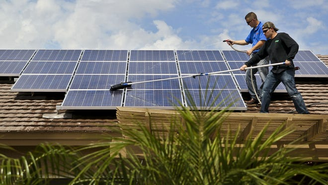 One Way Solar workers clean clean and rinse a solar array atop a Peoria home.