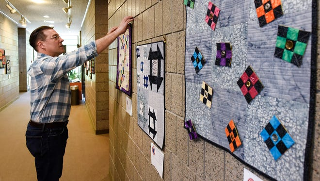 """Curator Eric Cheever works on a new exhibit of quilts Monday June 26, at the Stearns History Museum. The new exhibit titled, """"Granite City Rocks"""" features 24-by-24-inch quilts by the St. Cloud Heritage Quilters. The quilter had to use one of two fabrics that resemble granite in their creation."""