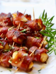 Easy Bacon Wrapped Scallops on a serving platter garnished with a sprig of rosemary.