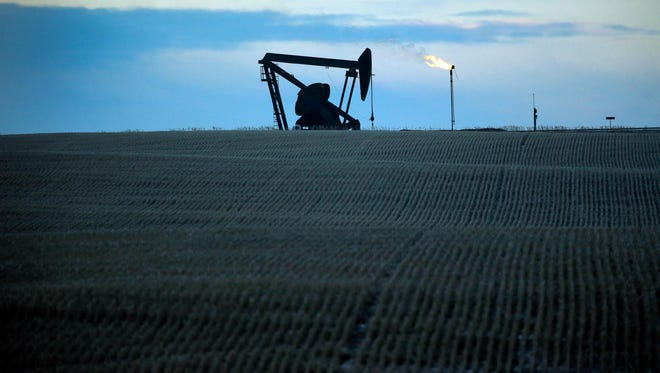 Gas is flared from a pumpjack near Williston, ND, in this Associated Press file art. Six of eight oil producing states are experiencing a recession, with Texas and Montana narrowly avoiding the same fate.