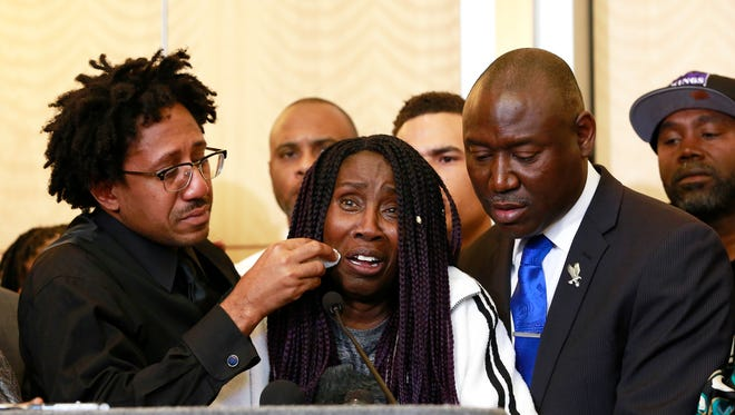 As Sequita Thompson, center, discusses the shooting of her grandson, Stephon Clark, Clark's uncle, Kurtis Gordon wipes a tear from her cheek during a news conference, Monday, March 26, 2018, in Sacramento.