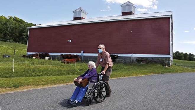 In this Monday, June 8, 2020, photo, 93-year-old Flo Young, originally from Cambridge, Mass., holds a box of pen pal letters as she takes a ride past a barn with activity aide Rich Vanderweit outside the Sullivan County Health Care nursing home in Unity, N.H. In a letter-writing effort during the virus pandemic to connect nursing home residents in two neighboring communities, residents now are receiving pen pal letters from across the United States.