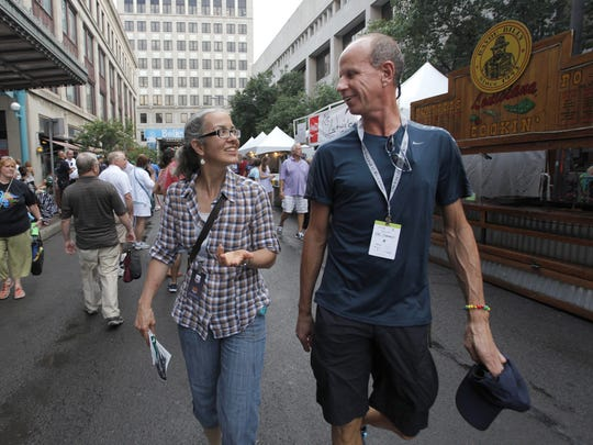 John Kralles, a registered dietician and certified diabetes educator at Rochester General Hospital, right, and Karen Miltner, left, make their way along Jazz St during XRIJF 2014. Kralles and Miltner were walking the jazz fest counting calories of jazz food .