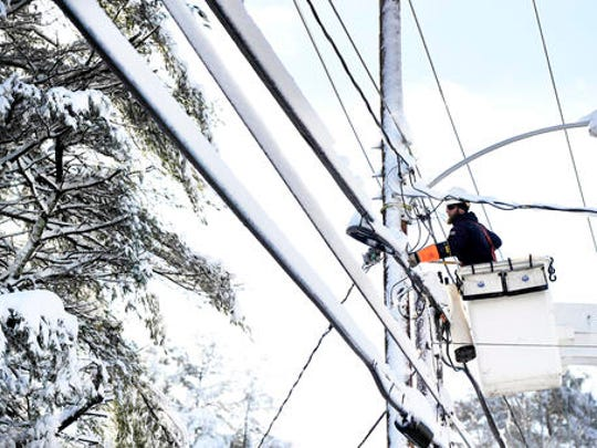 Justin Voight of On Target Utility works to restore power to a home along Main St. in Cumberland, Maine, Friday, Dec. 30, 2016. The most powerful nor'easter in nearly two years brought heavy snow, powerful winds and even thunder and lightning to northern New England, leaving tens of thousands of people in the dark Friday and burying some towns under 2 feet of snow.