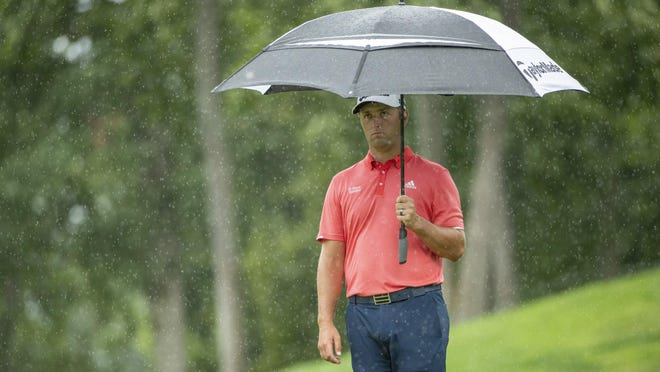 As rain begins to fall, Jon Rahm holds an umbrella while preparing for his next shot during the final round of the Memorial Tournament on Sunday. Rahm said one of his grandmothers and a great aunt died recently.