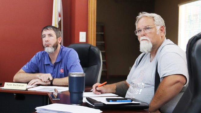 Chenoa City Commissioners Kyle Buchanan, left, and Dwayne Price listen to a comment being made from the audience during Tuesday's city council meeting.