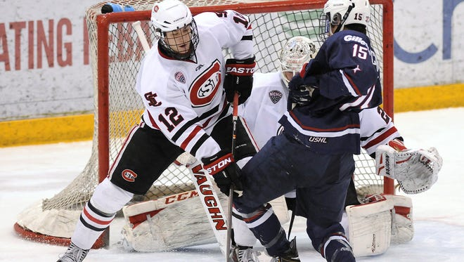 St. Cloud State defenseman Ethan Prow (12) tries to clear the puck away  in an exhibition game at the Herb Brooks National Hockey Center.