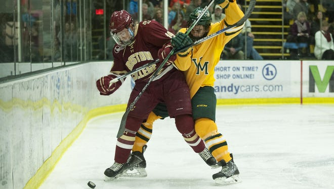Catamount defenseman Alexx Privitera (18) battles for the puck with Eagles' forward Ryan Fitxgerald (19) during the men's hockey game between the Boston College Eagles and the Vermont Catamounts at Gutterson Fieldhouse on Friday night in Burlington.
