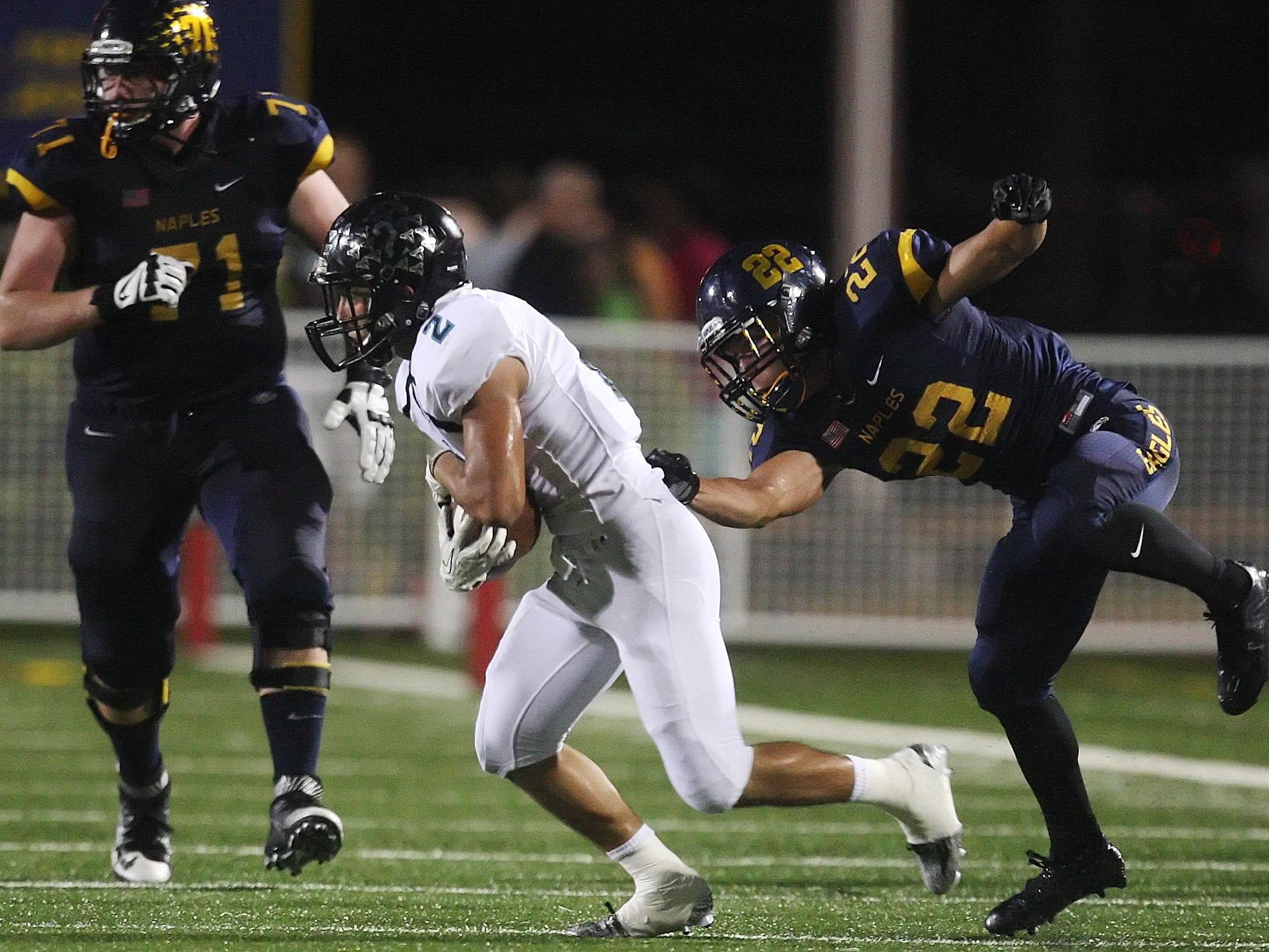 Gulf Coast High School's Vinny Deluca, center, intercepts a pass against Naples on Friday at Naples High School.