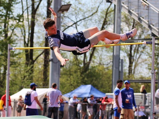 Livonia Stevenson's Ian Knoph scales the bar to win the high jump.