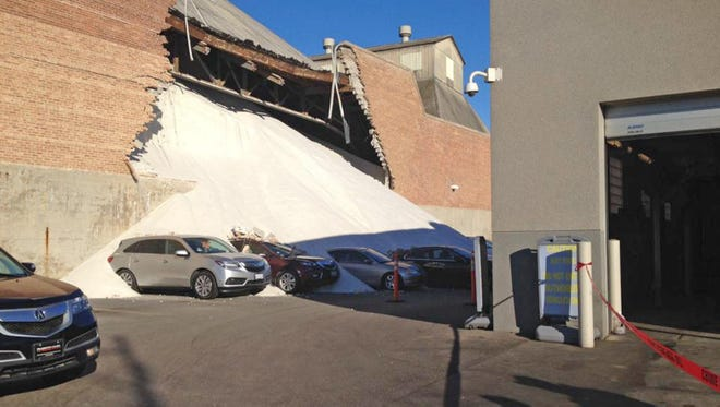 In this Tuesday, Dec. 30 2014, photo provided by The Chicago Fire Department, several cars at an adjacent auto dealership are buried in salt after a wall at a Morton Salt storage facility collapsed in Chicago. A Morton Company spokeswoman Denise Lauer said a side wall broke Tuesday on Chicago's northwest side, spilling road salt outside the facility and onto neighboring property. No injuries were reported.