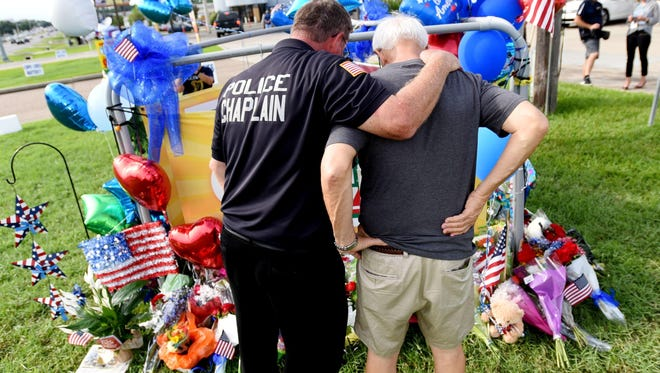 New Jersey Police Chaplain Bob Ossler, left, says a prayer with Mike Nola at a makeshift memorial in Baton Rouge, Louisiana on Monday, July 18, 2016. Multiple police officers were killed and wounded Sunday in a shooting near a gas station in Baton Rouge, less than two weeks after a black man was shot and killed by police, sparking nightly protests across the city.