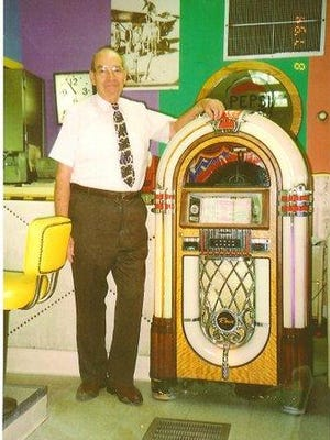 Mearle Heitzman stands next to the Jukebox in the old Mearle's College Drive-In.