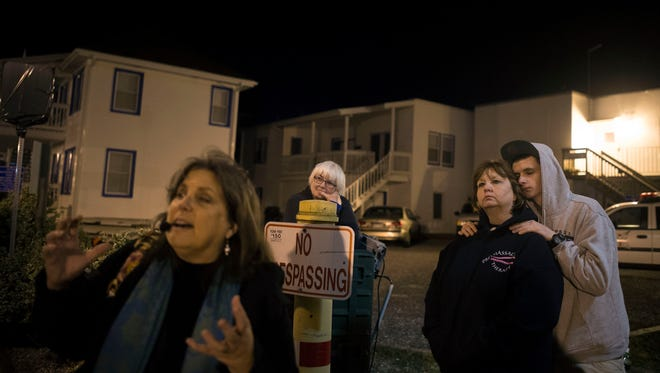 Chesapeake Ghost Walks guide Mindie Burgoyne, left, tells a story involving the suicide of a man at the Tarry-A-While guest house in Ocean City. His cigarette-smoking ghost is said to still haunt the building.