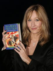 British author J.K. Rowling holds a copy of her latest