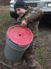 Tucker Hedge, 8, carries a bucket of fish as volunteers to stock trout at the western branch of the Conococheque Creek in Fort Loudon on Friday, March 9, 2018. Fishing season starts Saturday, March 31 in Franklin County.