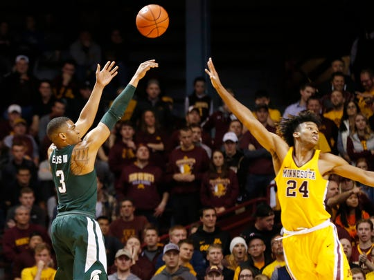 Michigan State's Alvin Ellis III, left, shoots over Minnesota's Eric Curry during the second half of MSU's 75-74 overtime win over Minnesota Tuesday in Minneapolis.