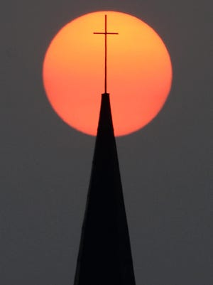 A hazy sun sets over Our Lady of Lourdes Church in Brockton, on Wednesday, Sept. 16, 2020. The smoke from dozens of wildfires in the western United States has now blanketed much of the country along with parts of Mexico and Canada, as residents thousands of miles away on the East Coast are being treated to unusually hazy skies and remarkable sunsets.