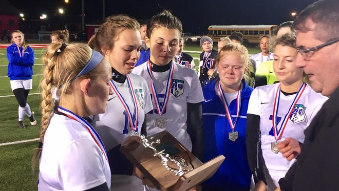 Zanesville's seniors accept the Division II district runner-up trophy following the Lady Devils' 1-0 loss to New Philadelphia on Thursday at Coshocton's Stewart Field. Zanesville loses eight seniors off a team that finished 12-4-3.