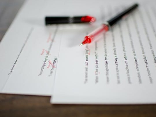 A red pen sits on papers with red edit marks.