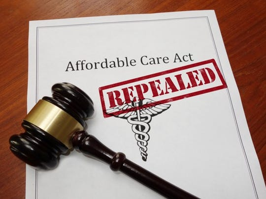 """An Affordable Care Act plan stamped with the word """"Repealed"""" next to a judge's gavel."""