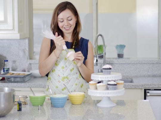 Woman decorating a cupcake