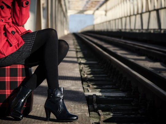 A well-dressed is seated in a train station.