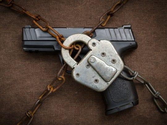 A gun secured by a padlock.