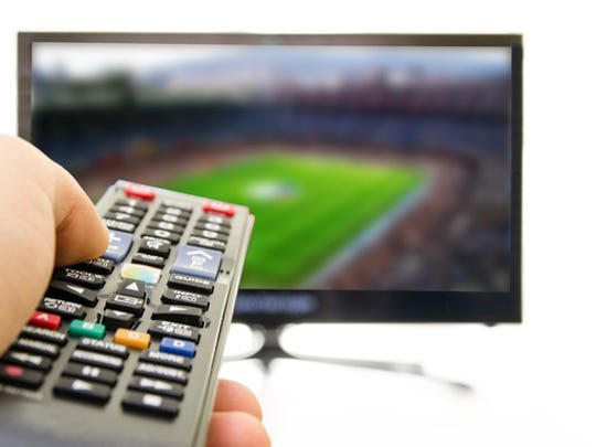 A big-screen TV displaying a sporting even in the background. In the foreground, someone is holding a TV remote controll.
