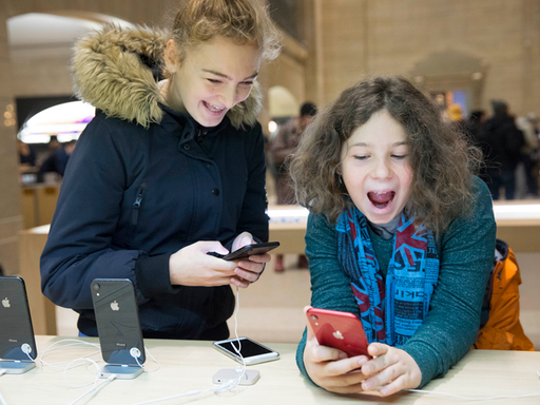 Two young children playing with the Apple iPhone XR in an Apple store.
