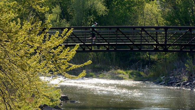 A runner jogs over Skunk Creek in Dunham Park Friday evening, May 16, 2014.