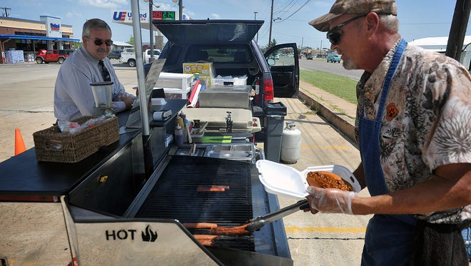 Don Finley, left, watches as Brian Lemmond puts together a chilidog at his cart in the parking lot of United Supermarket on Jacksboro Highway Wednesday, National Hot Dog Day.