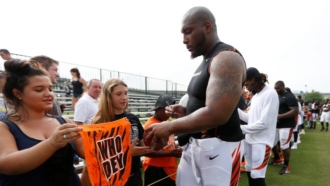 Cincinnati Bengals defensive tackle Devon Still signs autographs for fans after training camp downtown.